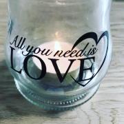 Glas Lysestage med teksten All you need is love. Der er et tændt fyrfadslys. Det står på et træbord.